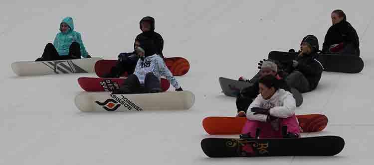 sitting snowboarders